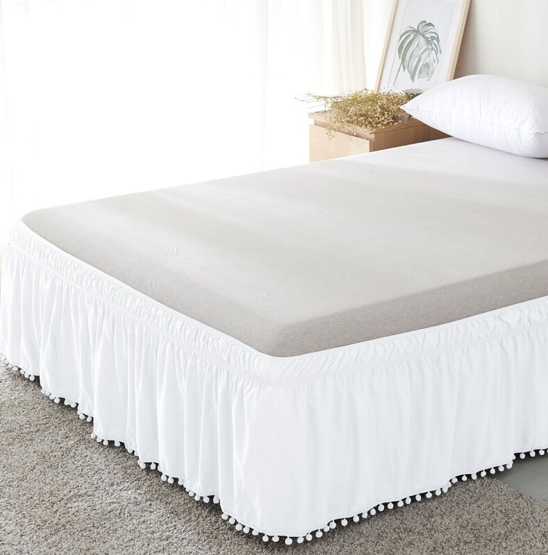 A white bed skirt with pom pom fringe is a fun addition to white bedding in a white bedroom.