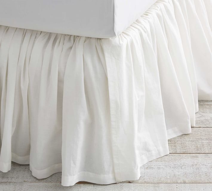 A voile white bed skirt matches white bedding in a romantic bedroom.