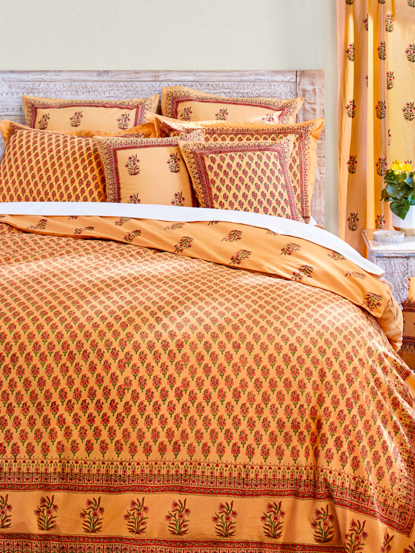 Orange tropical bedding with an Indian print is bedding that goes nicely with a neutral or green bed skirt.