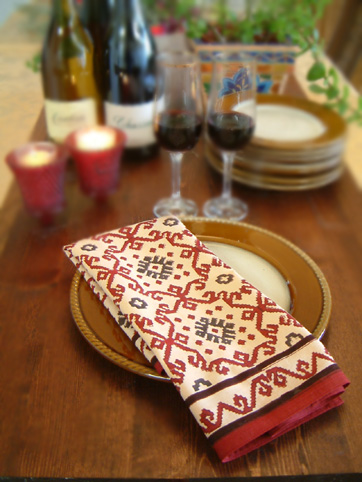 block printed cloth napkin in red, black, and cream on a table set with gold plates and glasses of red wine