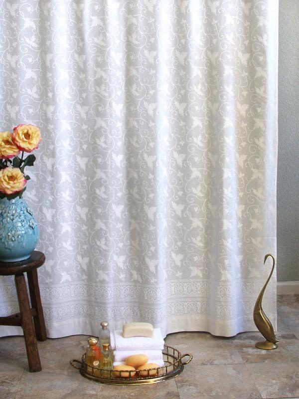 White shower curtain with ivy pattern and lace print in the bathroom.