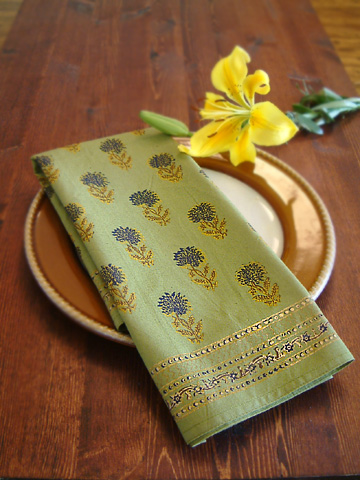 Elegant green cloth napkins with gold accents sits upon a table near a yellow flower.