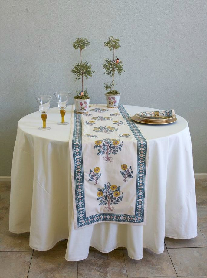 A floral table runner on a round table over an off-white tablecloth