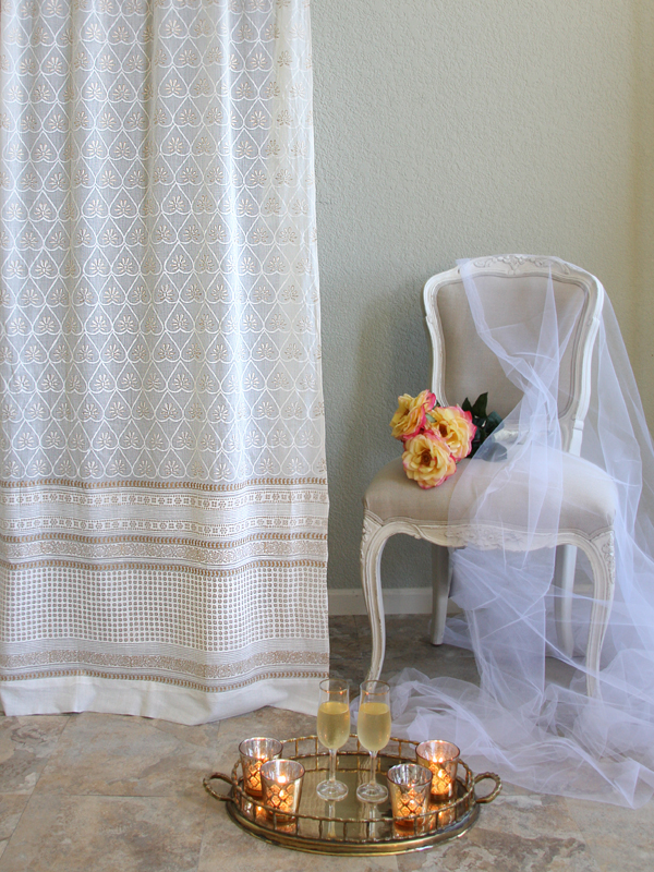 gold and white sheer curtain with pattern beside yellow home decor, bouquet, and candles and champagne