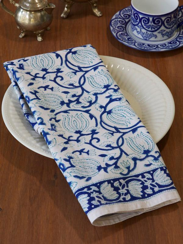 Blue hawaiian flowers, like in our Midnight Lotus summer tablecloths, grace a cloth dinner napkin at an elegant table setting.