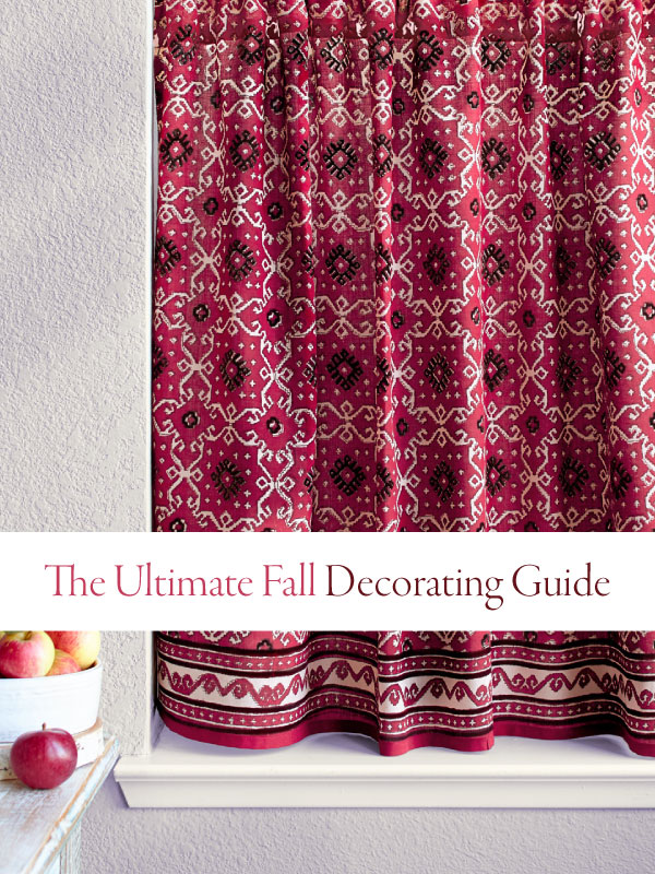 ultimate fall decorating guide banner over red curtains and near a bowl of apples