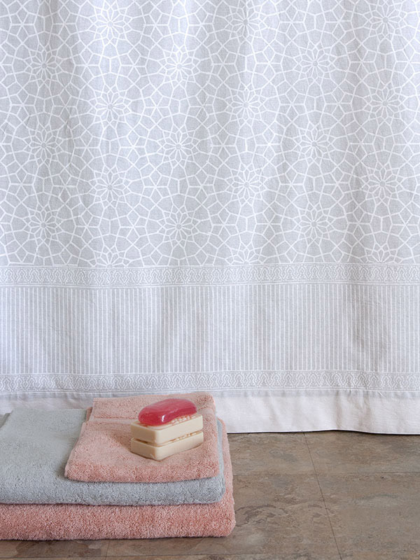 white shower curtain with block print pattern, towels and soap beside it, for spa gift baskets