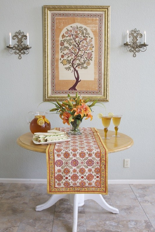 A floral orange table runner on a round table