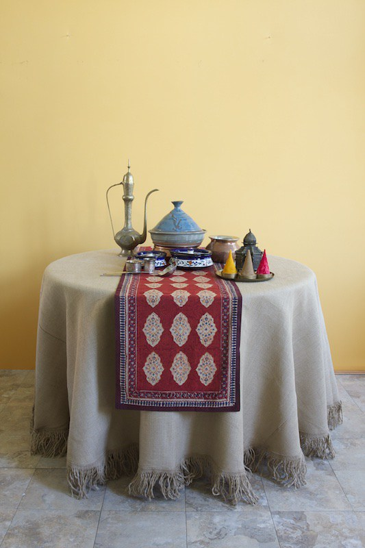 A red table runner on a round table covered with a neutral tablecloth