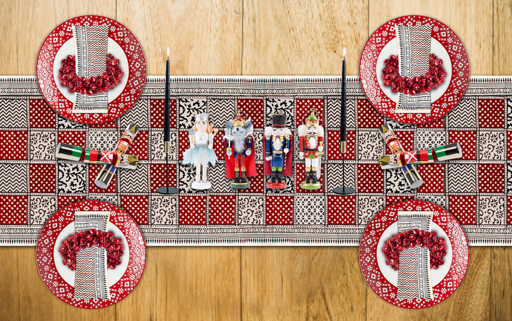A colorful Christmas table set with a red Christmas table runner