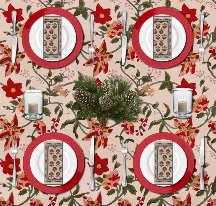A colorful Christmas table set with a vintage Christmas tablecloth