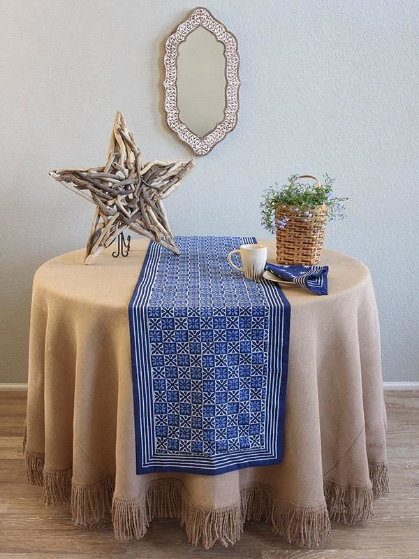 A blue table runner on a round table with a neutral tablecloth