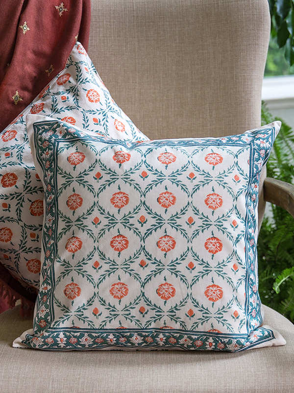 An orange cream and green pillow cover in a floral pattern