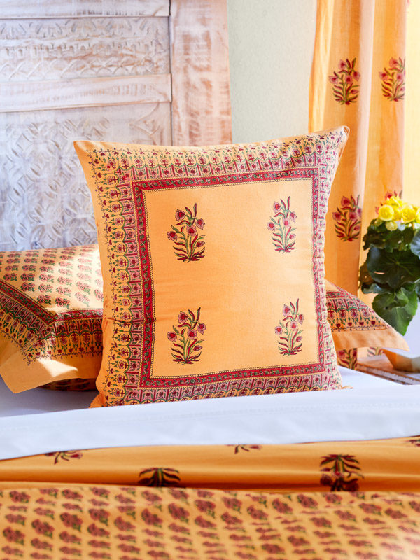An orange bedroom with a floral pillow cover in a happy home