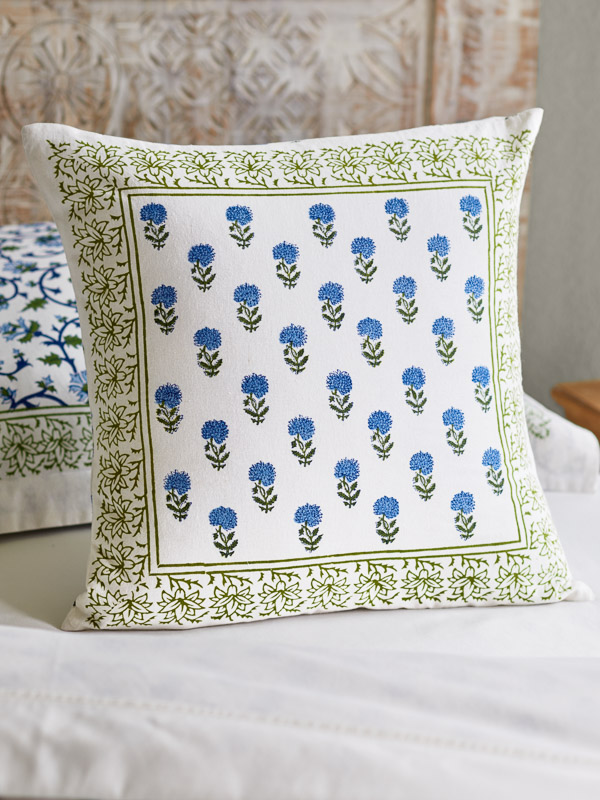 A throw pillow in a blue floral print rests upon a bed.