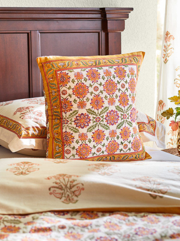 orange throw pillows with floral print in a bedroom style with other orange decor and wood bed frame