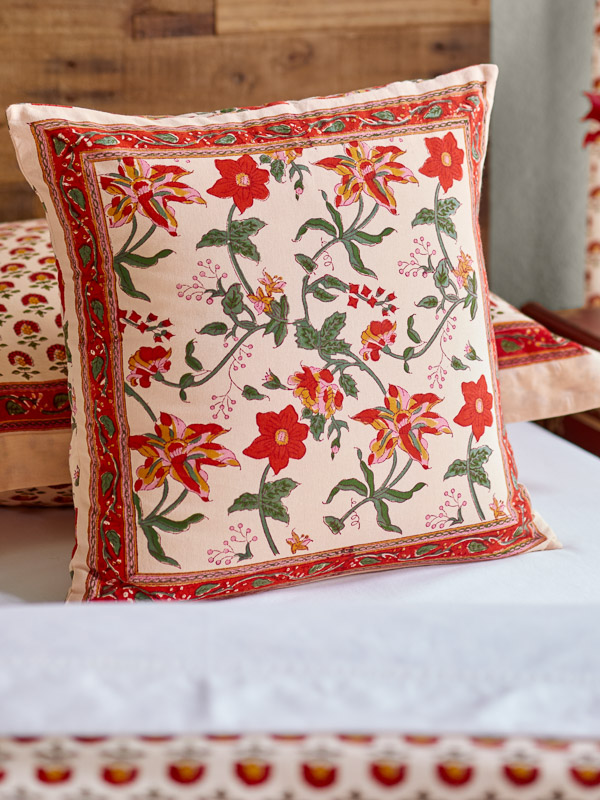 A tropical print floral pillow pairs with orange decor and white sheets