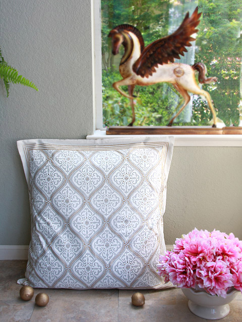 gold and white pillow in a block print with a bowl of pink peonies beside it
