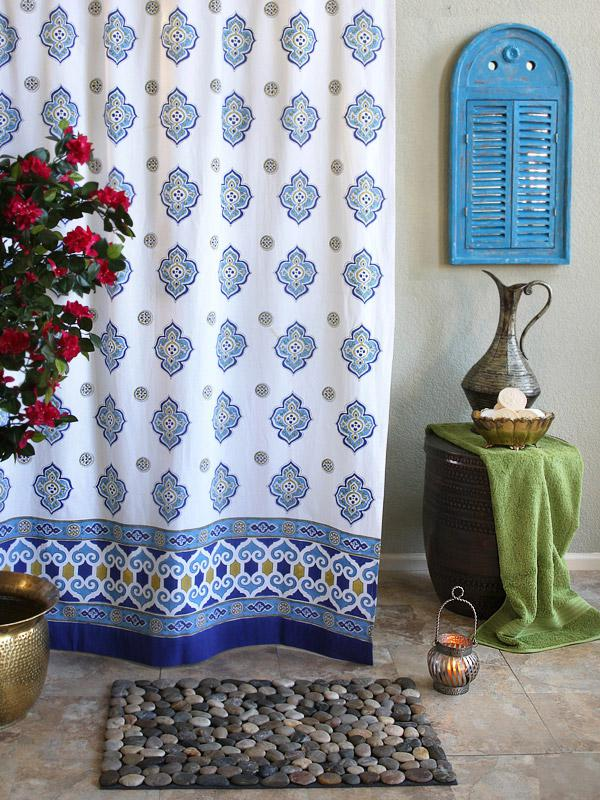 A white and blue Moroccan shower curtain hangs in a bathroom styled like coastal interiors.