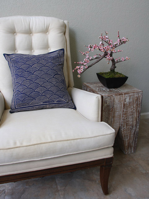A navy blue throw pillow rests on an off-white armchair beside a mini cherry blossom plant for elegant coastal decor.