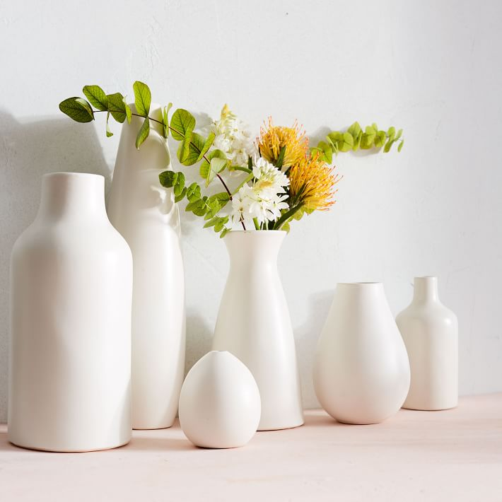 a collection of simple white ceramic vases, one filled with a green, yellow, and white floral mix