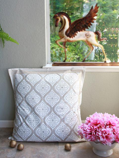 A white pillow with gold accents and pink peonies