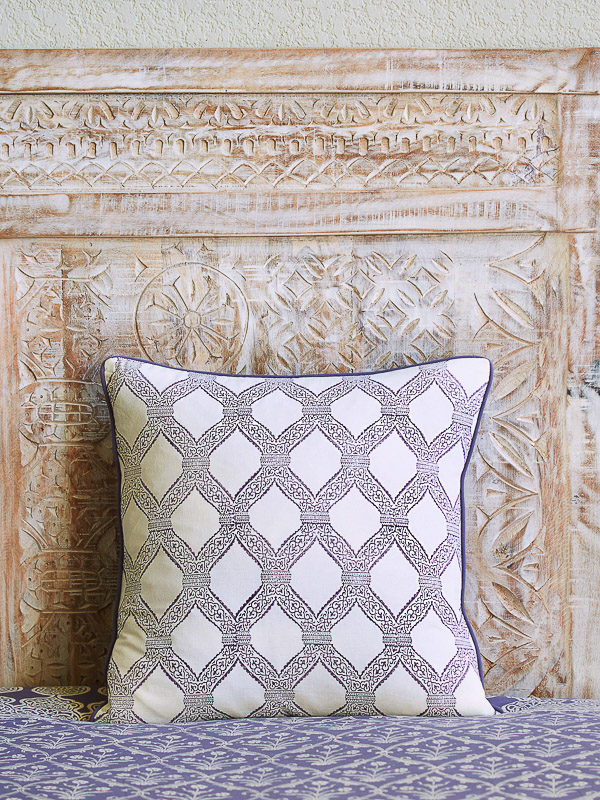 white boho pillow cover with lilac color trellis pattern over a lavender bedspread