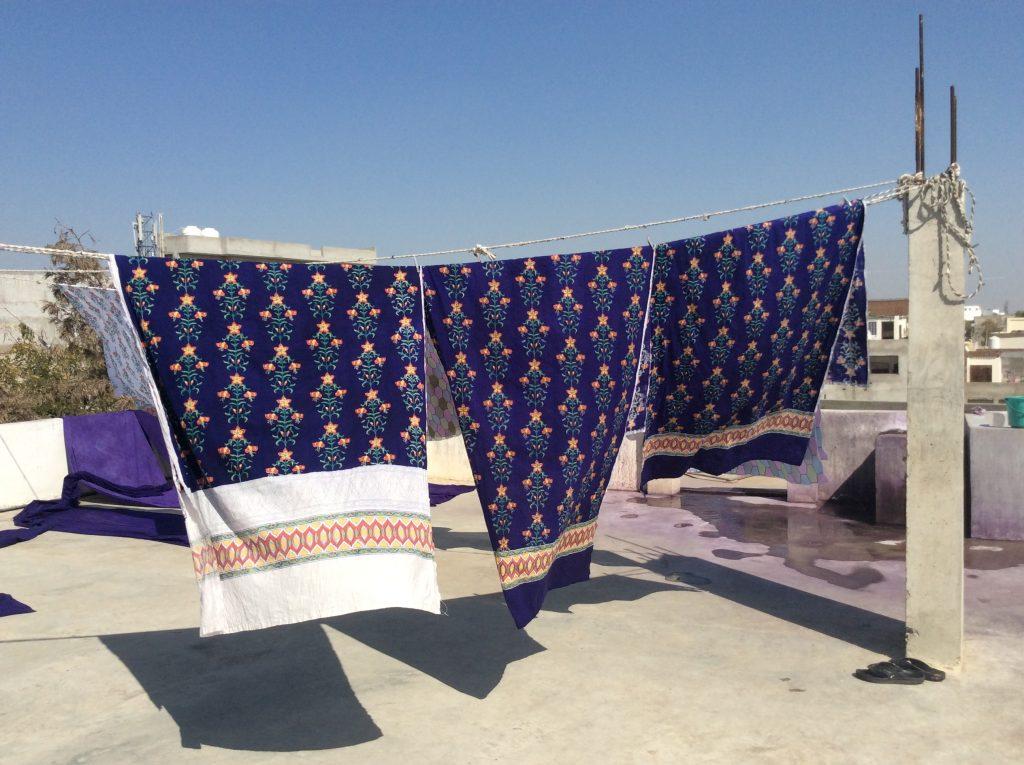 block print fabric line drying in the sun