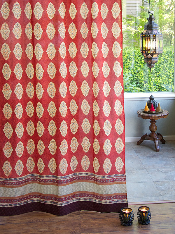 sheer curtain panel with floral filigree of cinnamon, turmeric and imperial blue with motifs on a red orange ground