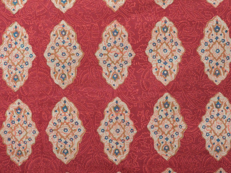 floral filigree of cinnamon, turmeric and imperial blue on a rich red orange ground