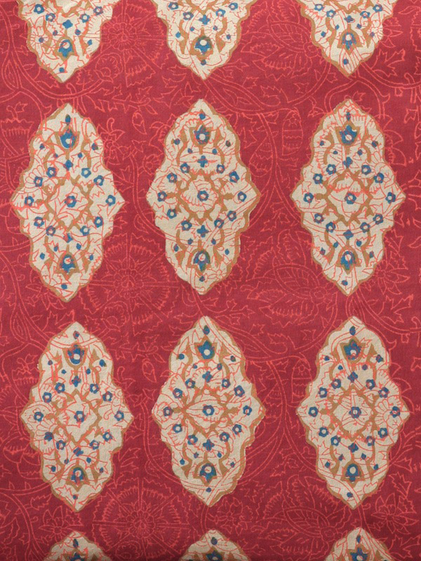 floral filigree of cinnamon, turmeric and imperial blue with motifs on a red orange ground