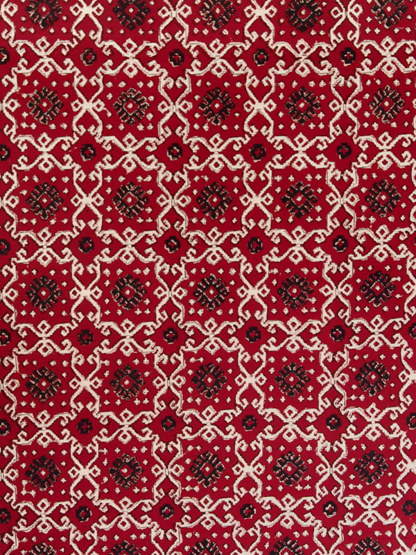 A bold dramatic black and tan kilim inspired geometrical print grounded in deep ruby red