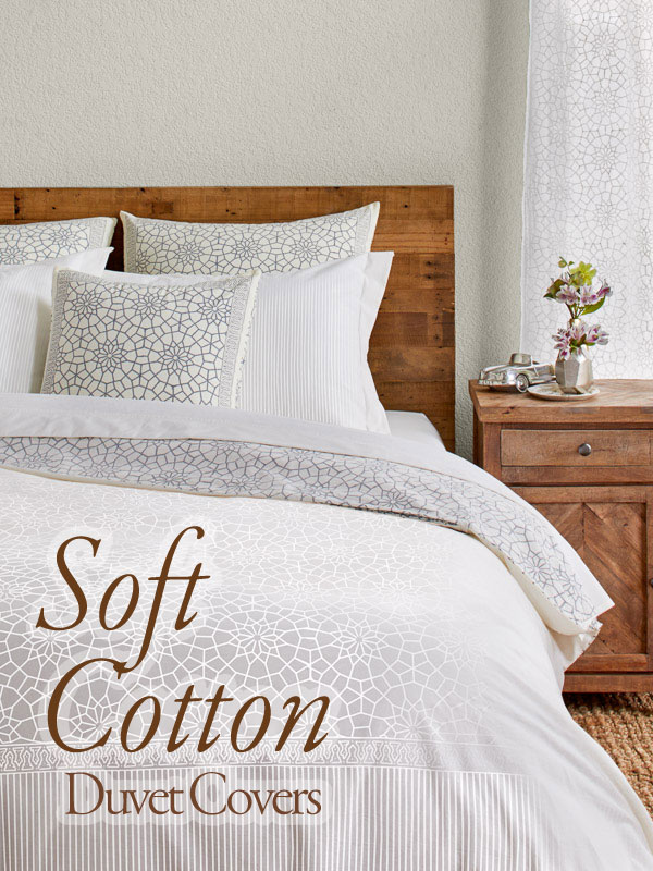 Bed made with a soft white cotton duvet cover and bedding from India