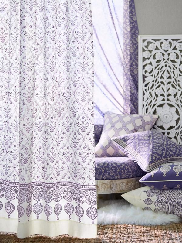 lilac color pillows piled near a window with white and purple curtains in a romantic style elegant floral pattern