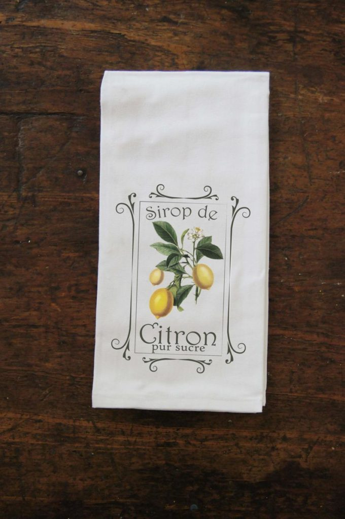 A tea towel with a French saying and lemon print as cheerful yellow decor for the kitchen