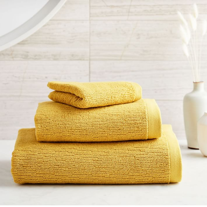 yellow decor: mustard yellow towels in grey and yellow and white bathroom