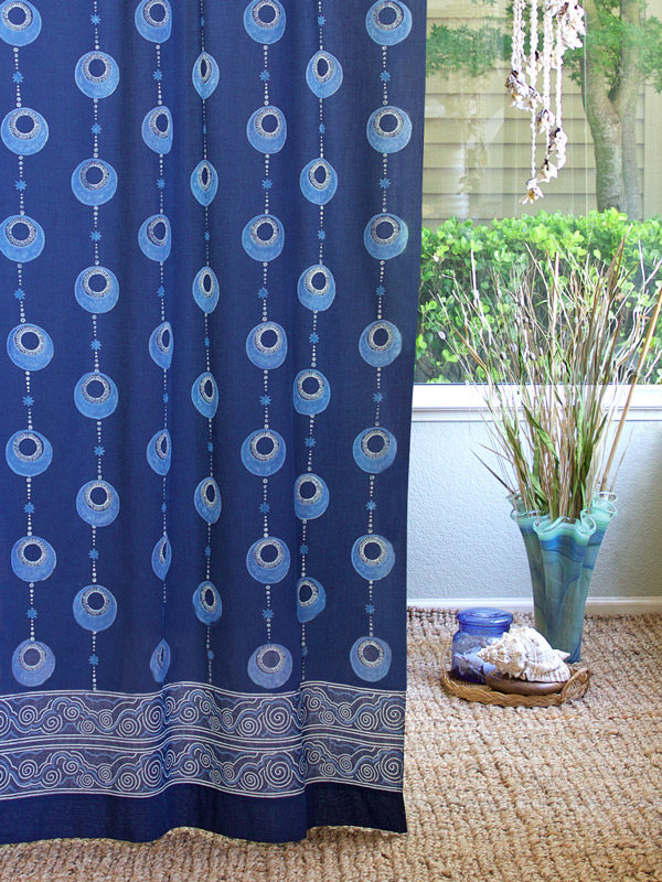A vintage island style curtain with a blue bohemian pattern hangs at the window, making for elegant coastal decor.