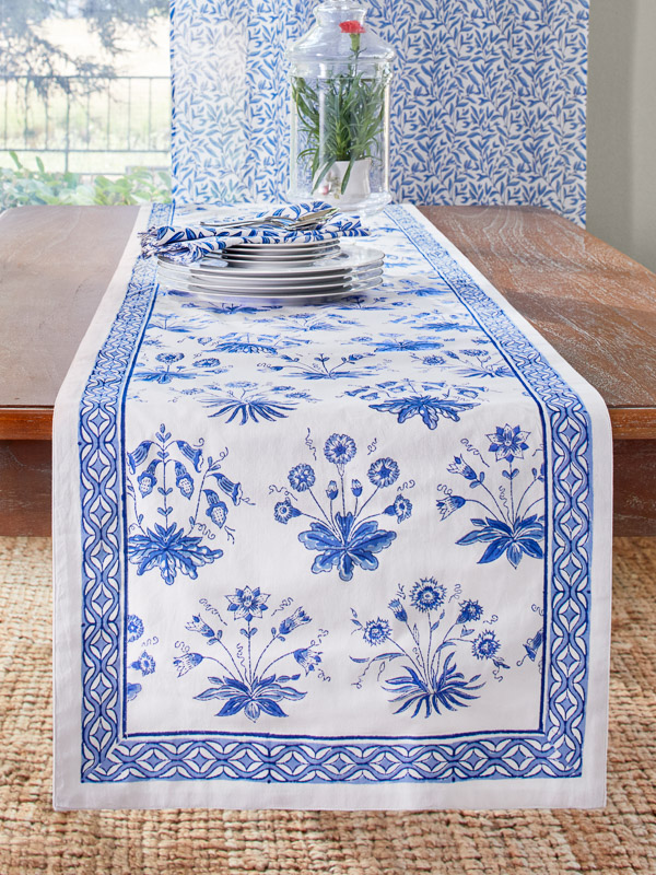 A blue and white table runner with a floral pattern in English cottage style on a wooden table
