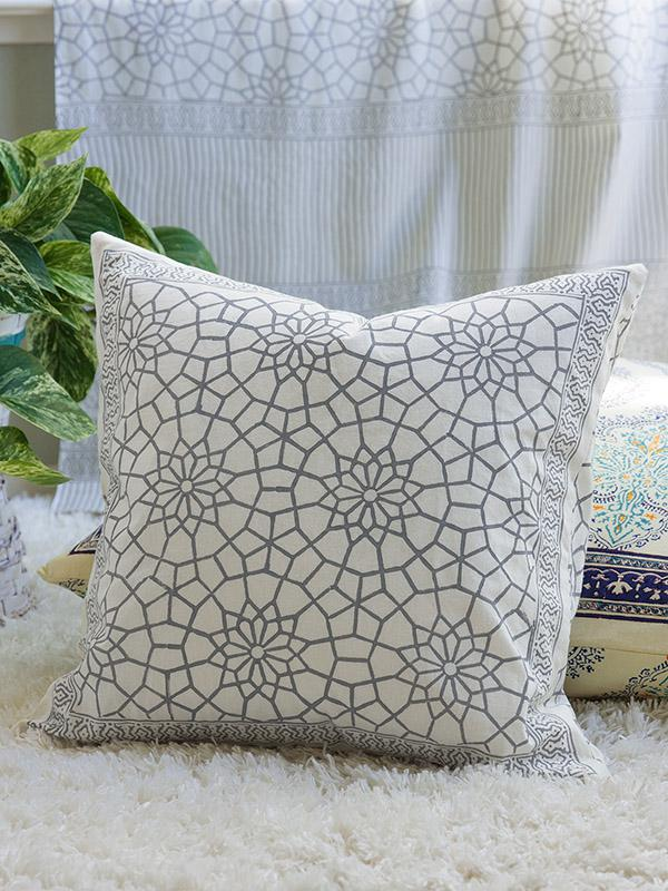 grey and white throw pillow on a white flokati rug with white sheer curtains in the background