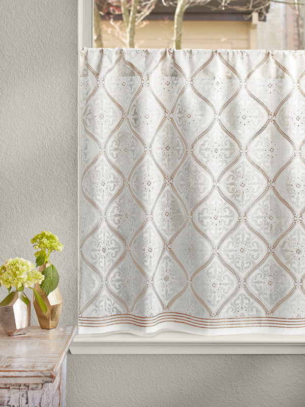 This gold and white cafe curtain hangs at the kitchen window as a lovely kitchen window treatment.