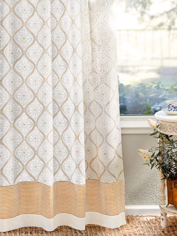 White and gold curtains frame the window in a glam living room