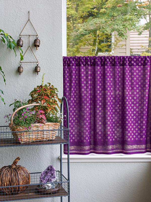 Purple cafe curtains hang near plants and bells in a zen room