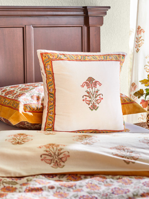 a block print pillow featuring an elegant floral pattern in cream, orange, and green