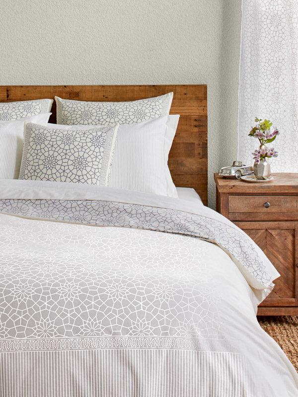 A bed is dressed in a Moroccan duvet cover with white pillows in a medallion print.