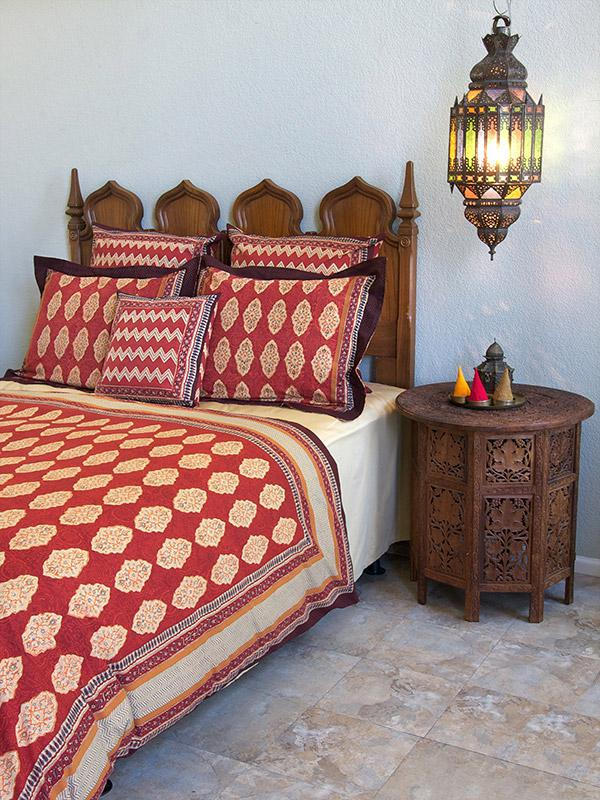 Red Moroccan bedding is boho bedding, especially with a lantern hanging beside the bed.