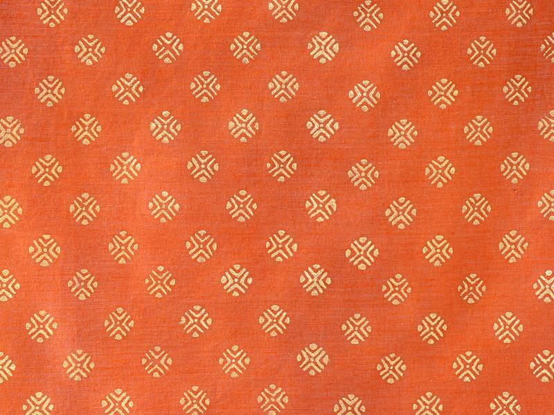 Indian sari print pattern on fabric, orange with gold stamp