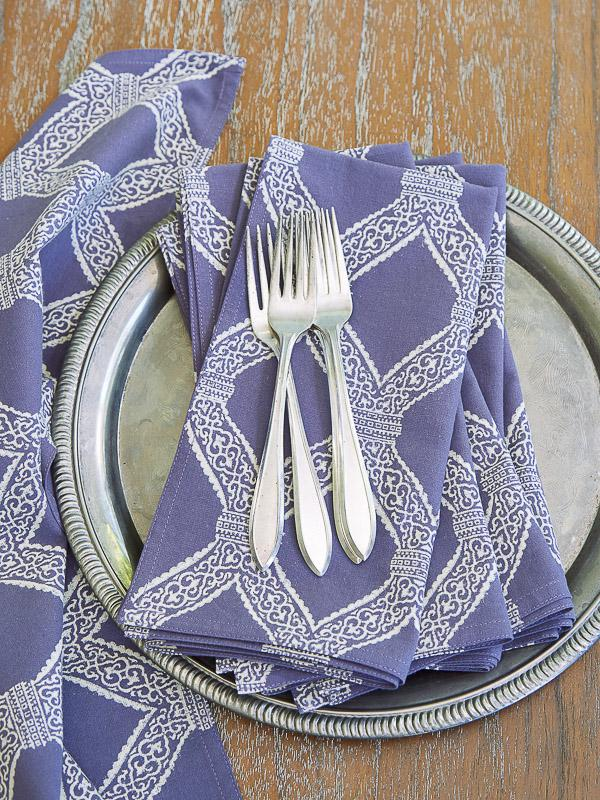 purple cloth napkins on a silver platter with cutlery to go with a purple Valentine tablecloth