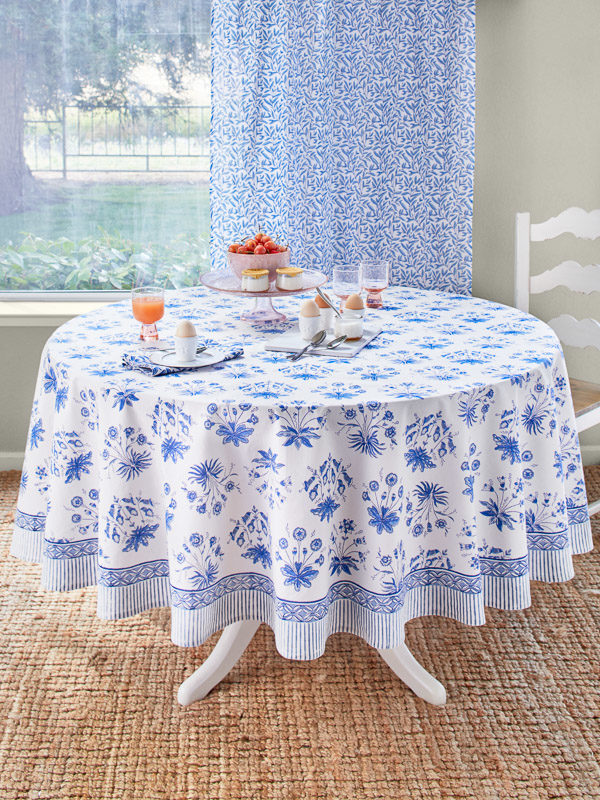 A white and blue floral tablecloth covers a table in an English cottage style breakfast nook.