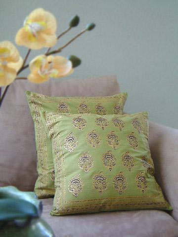 Green throw pillows with gold accents dress up a side chair.