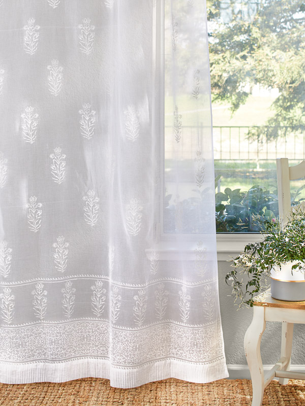 White sheer curtains with floral patterns grace a window with a garden view.